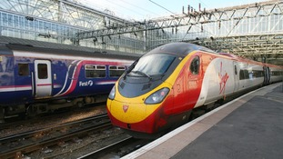 A FirstGroup service passing a Virgin Pendolino train in Glasgow Central Station