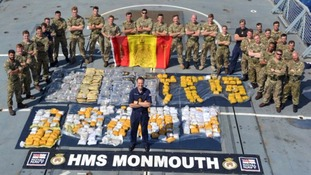 Royal Navy and Royal Marines Boarding team, with Cdr Ian Feasey, Commanding Officer, HMS Monmouth (centre) and the recovered drugs haul.