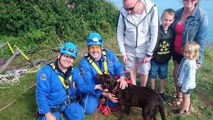 Coastguard rescue team with dog and family