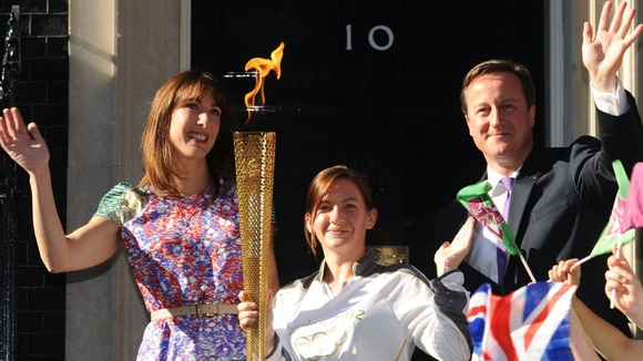 Samantha Cameron and David Cameron stand either side of Olympic Torch bearer Kate Nesbitt in their Christmas card.