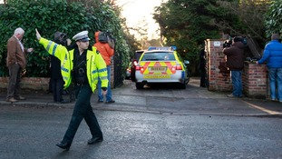 Police and the media outside Stuart Hall's home in Wilmslow, Cheshire.