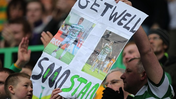 Celtic fans hold up a banner in support of former player