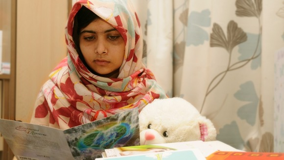 Malala Yousafzaireads a card as she recuperates at the The Queen Elizabeth Hospital in Birmingham in October