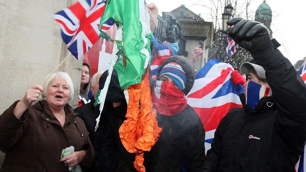 A masked protester attempts to burn an Irish tricolour in Belfast city centre.