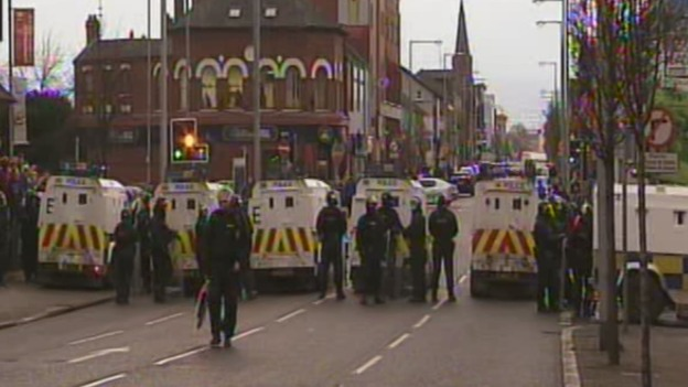 Police in riot gear line the streets of Belfast during the flag protest.