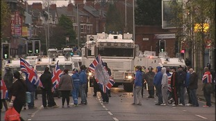 Protesters waving Union flags are faced with a heavy police presence in Belfast.