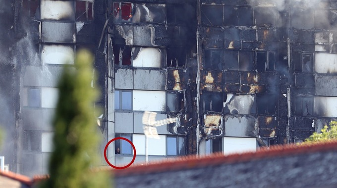 A man (circled) was seen looking from a window as smoke poured from the fire.