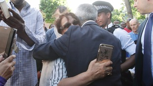 London Mayor Sadiq Khan hugs a woman near Grenfell Tower.