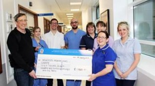 Thomas McManus presents cheque to Staff Nurse Rachel Carr, VAD Specialist Nurse Andrew Wood, Staff Nurse Jonathan Stokel, Sister Deborah Perry, Matron Lisa Guthrie, Staff Nurse Suzie Crumpton and VAD Nurse Practitioner Nicola Robinson Smith.