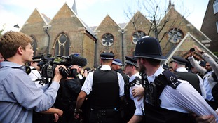 Police struggle to hold back the crowd which surrounded Theresa May's car during her visit to Kensington.