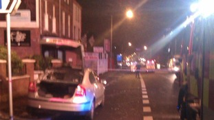 The petrol-bombed car is pictured and surrounded by police personnel in Belfast.