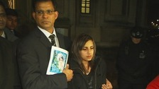 Benedict Barboza holds a picture of his wife, Jacintha Saldanha, and stands with their daughter outside the House of Commons