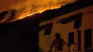 A man on the balcony of a house looks up at a forest fire raging on a hillside above the village of Avelar.