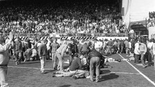 Fans on the pitch receive attention after severe crushing at Hillsborough during a Liverpool and Nottingham Forest match in 1989.