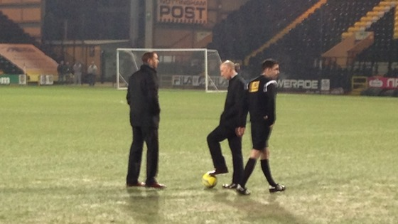 Officials inspect the pitch