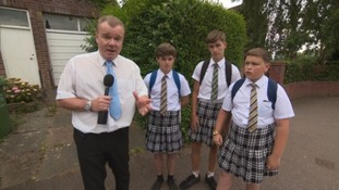 reporter with boys in skirts