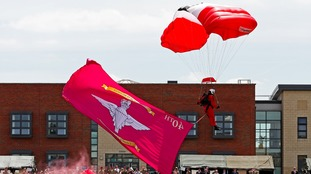 A member of the Red Devils Parachute Regiment lands with a commemorative flag in Colchester.