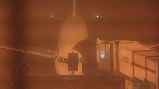 A plane seen through the fog blanketing Heathrow Airport