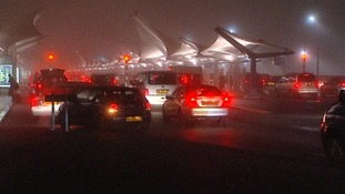 Cars wait in the fog to drop off passengers