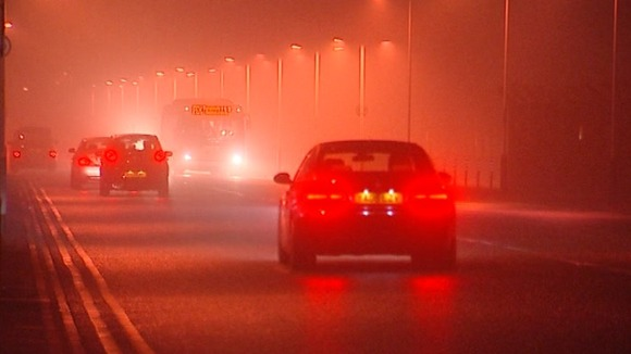 Cars and buses make their way through the fog around Heathrow Airport