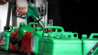 A man uses petrol pumps to fill petrol cans