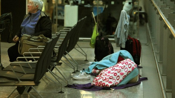 Passengers sleep as they prepare to depart from Terminal 5 at Heathrow Airport