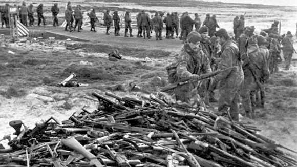 Argentine soldiers line up to hand in their weapons to Royal Marines near Port Stanley.
