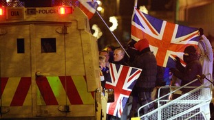 Loyalist protestors carrying Union flags clash with police outside the City Hall in Belfast