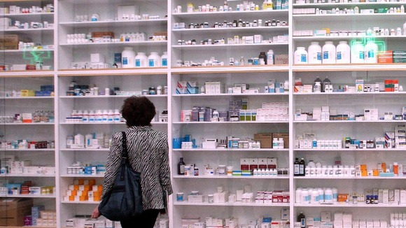 A woman looks at the gallery-sized installation 'Pharmacy'.