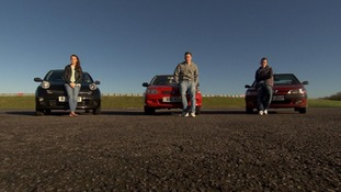 3 young people stood next to their car on a racetrack