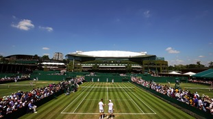 A warm and sunny day at Wimbledon as spectators watch a game of doubles