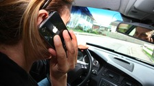 The illustration shows a woman driving her car while talking on her mobile phone.