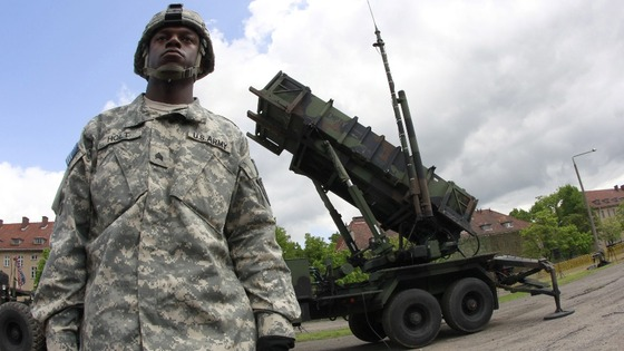 A US soldier stands next to a Patriot surface-to-air missile battery at an army base in Morag, Poland.