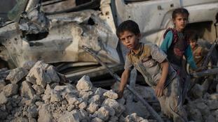 Children flee through the rubble