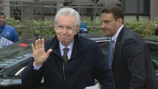Italian Prime Minister Mario Monti waves as he arrives at the venue in Brussels
