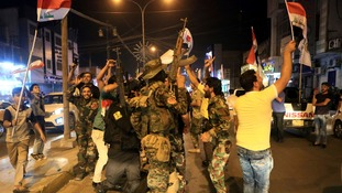 Iraqi security and civilians dance in the streets together.