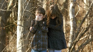 Young children wait outside Sandy Hook Elementary School after the shooting