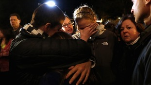 People grieve outside the vigil at the Saint Rose of Lima church in Newtown, Connecticut