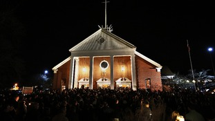 People stand outside a vigil at the Saint Rose of Lima church in Newtown, Connecticut