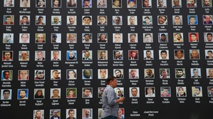 A man walk past a poster of photographs of victims of the July 15, 2016 coup attempt.