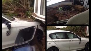 Man injured as car smashes through living room wall