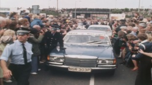 Car surrounded by crowds of people