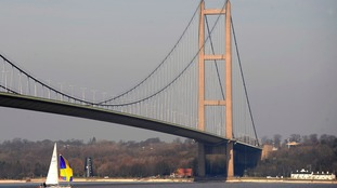 A sailing boat goes under the Humber Bridge on the Humber estuary, near Kingston upon Hull.