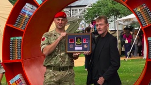 1st regiment Royal Military Police Lt Col Mark John (Catterick's Jack Reacher lookalike) hands over a plaque to author Lee Chil