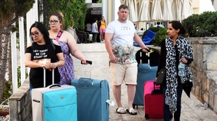 Tourists leave their hotels after an earthquake hit parts of Turkey and the island of Kos