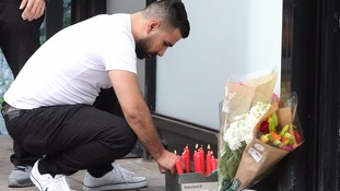 A man leaves flowers at the scene where Mr Charles died.