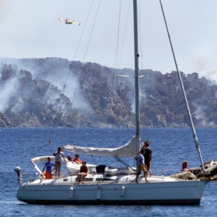 Holidaymakers watched as planes tackled the smoking hillside near the popular resort of Saint-Tropez.