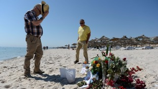 A tourist pays tribute at the scene of the massacre in Tunisia.