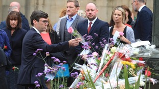 Mayor of Greater Manchester Andy Burnham left a flower to a tribute pile after joining mourners at the service.