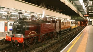 Steam train on London Underground tracks.